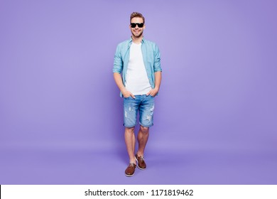 Full body size length of attractive trendy stylish positive cheerful man holding hands in pockets, wearing denim, over pastel violet purple background