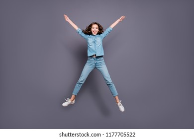 Full body size length of nice crazy stylish cheerful attractive adorable brunette girl with wavy hair in casual denim shirt and jeans, jumping in air like star figure, isolated over grey background