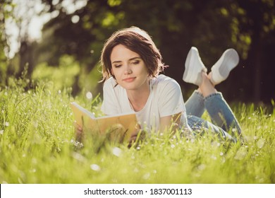 Full body size photo of charming lovely cute lady smiling reading nice romantic novel textbook lying grass in harmony world nature resting wear jeans sneakers white shirt outside