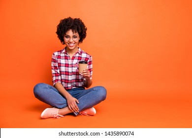 Full body size photo pretty lady sit floor hold hands paper coffee mug rest legs crossed wear specs casual checkered plaid shirt isolated orange background