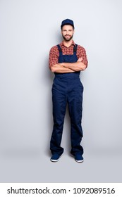 Full body size portrait of handsome attractive mechanic with stubble in blue overall, shirt, cap having his arms crossed, looking at camera, isolated on grey background