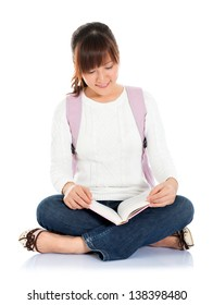 Full body of smiling Asian college student sitting on floor, isolated on white background