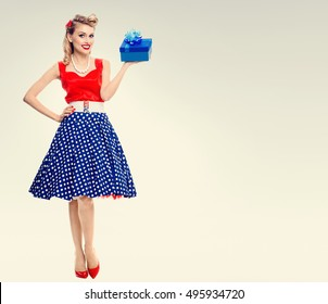 Full body of smiling woman dressed in pin-up style dress with polka dot. Caucasian blond model posing in retro fashion and vintage concept shoot. Copyspace area for advertising slogan or text message.