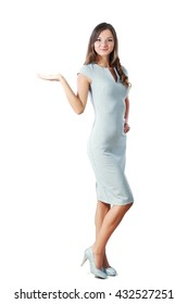 Full body of a standing woman in grey dress pointing at side isolated on a white background