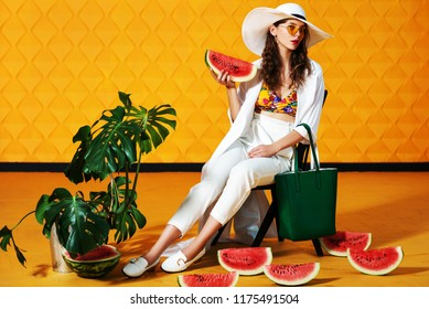 Full body studio fashion portrait of young beautiful model wearing long white trench coat, trousers, wide-brimmed hat, loafers, yellow sunglasses, holding green bag, posing on  background. Copy space