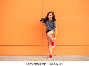 Full Body of trendy girl with vintage camera putting on red sneakers on orange background