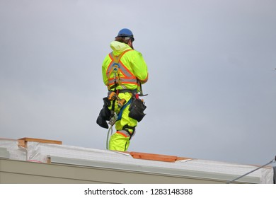 Full body view of a construction worker and his safety reflective apparel and tools.