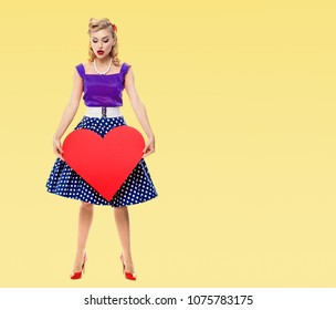 Full body of woman holding red heart symbol, dressed in pin-up style dress with polka dot, with copyspace area for slogan or advertising text message, on yellow background. Retro and vintage concept.