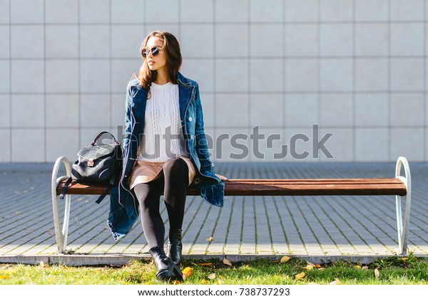 Full body of woman portrait in sunglasses and jeans trench coat sitting on the bench, looking aside and smiling. Beautiful young multiracial woman relaxing in urban city background.