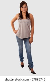 Full body of a young attractive brunette teen wearing high heels and jeans standing over white