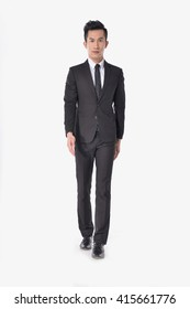 Full body young businessman walking in studio