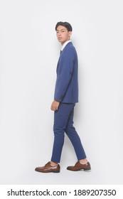 Jugendlicher-Vollmann  mit blauem Anzug, Krawatte mit weißem Hemd und blaue Hose mit braunen Lederschuhen im Studio