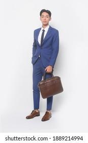 Jugendlicher-Vollmann  mit blauem Anzug, Krawatte mit weißem Hemd und blaue Hose, die eine schwarze Handtasche mit Turnschuhen hält