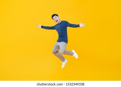 Full body of young dynamic handsome Asian man smiling and jumping with arms outstretched  isolated on yellow background