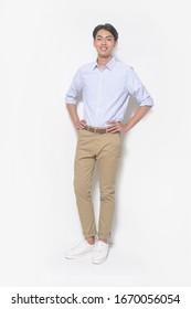 Vollkörperjunge Handsome Mann mit gestreiftem, langärmeligem Hemd, Khaki Hose, weißen Turnschuhen, Händen auf Tasche,