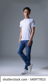 Full body young man in jeans posing on gray background