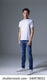 Full body young man in shirt with jeans standing on gray background