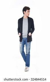 Full body young man standing in jeans walking on white background