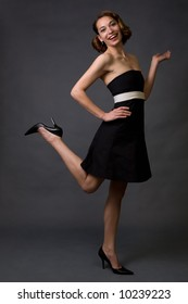 Full body of young pretty brunette woman modeling short strapless black dress while standing on grey background with happy expression and standing on one leg and one hand held out flat