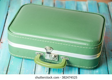 full boho suitcase on a distressed blue background
