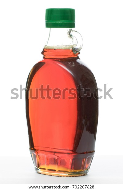 a full bottle of maple syrup on white background