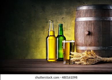 Full bottles of beer and glass with barrel against a dark background
