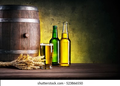 Full bottles of the beer and glass with barrel against a dark background