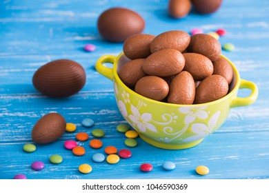 Full bowl of Easter chocolate eggs with color dragee on  a wooden background
