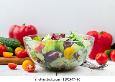 Full bowl of fresh green salad close up on a light table against a white background on a rustic kitchen. Concept helpful and simple food