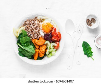 Full bowl healthy food - buckwheat, baked sweet potatoes, spinach, egg, beetroot, celery, tomatoes. Nutritious diet lunch on light background, top view