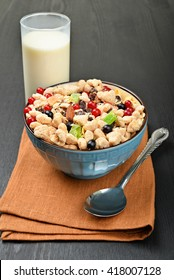 full bowl of muesli with berries and spoon on a napkin near to the glass of milk on a dark wooden background