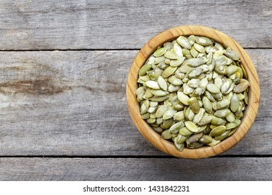 Full bowl of pumpkin seeds close up on a wooden table. Top view
