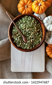 Full bowl of pumpkin seeds closeup on a cutting board with colorful pumpking around - Image