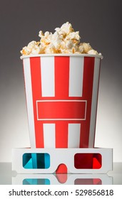 Full box of popcorn and 3D glasses on a gray background