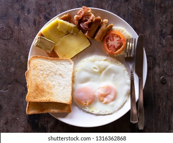 full breafast fried eggs with tomato, pineapple, ham, becon, cheese, bread & butter. top view