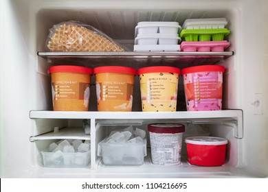 Full of bucket container ice creams flavors and ice cubes in freezer get ready for summer.