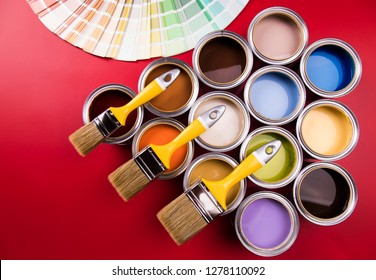 Full Buckets of rainbow colored oil paint on red background