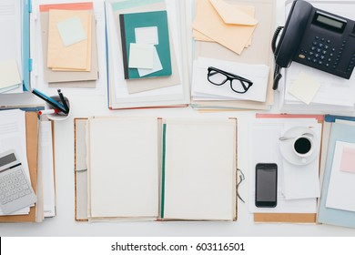 Full business desktop with paperwork, telephone and an open folder with blank pages, top view