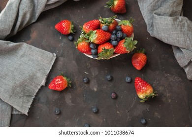 Full of ceramic bowl with blueberries and strawberries  on the stone table. And a hand dropping pieces of blueberries from the air