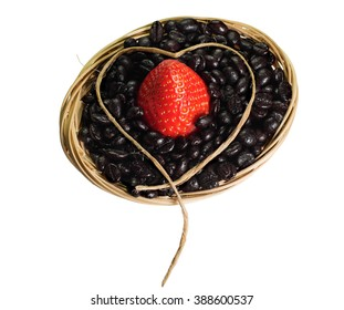 Full of coffee beans basket with ripe red strawberry in the middle and decorated with heart.