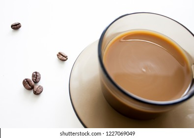 Full coffee cup with coffee beans on white background. Coffee still life.