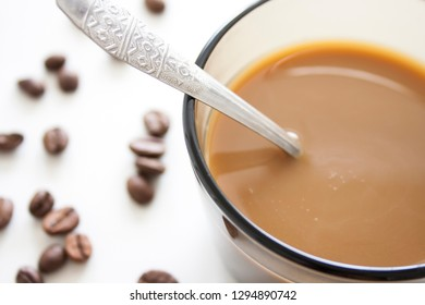 Full coffee cup with spoon and roasted coffee beans on white background. Coffee still life.