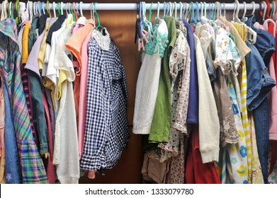 Full of colorful clothes arranged on closet for kids. Cluttered child wardrobe.