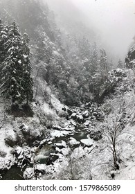 Full colour, snow-covered and icy river valley at the foot of the road leading to Bristen, Switzerland.