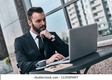 Full concentration. Good looking young man in full suit using computer and keeping hand on chin while sitting in the cafe outdoors