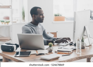 Full concentration. Handsome young African man working on the computer and smiling while sitting at his working place in creative office