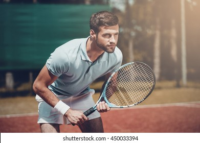 Full concentration. Handsome young man in polo shirt holding tennis racket and looking concentrated while standing on tennis court