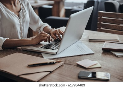 Full concentration at work. Close-up of African woman using computer while sitting in cafe