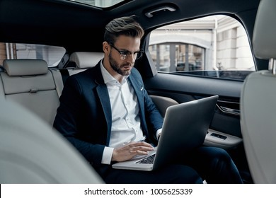 Full concentration at work. Confident young man in full suit working using laptop while sitting in the car
