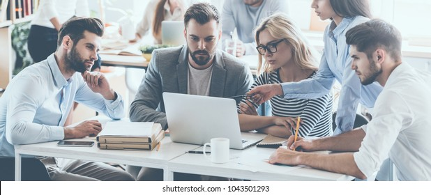 Full concentration at work. Group of young business people working and communicating while sitting at the office desk together with colleagues sitting in the background - Shutterstock ID 1043501293